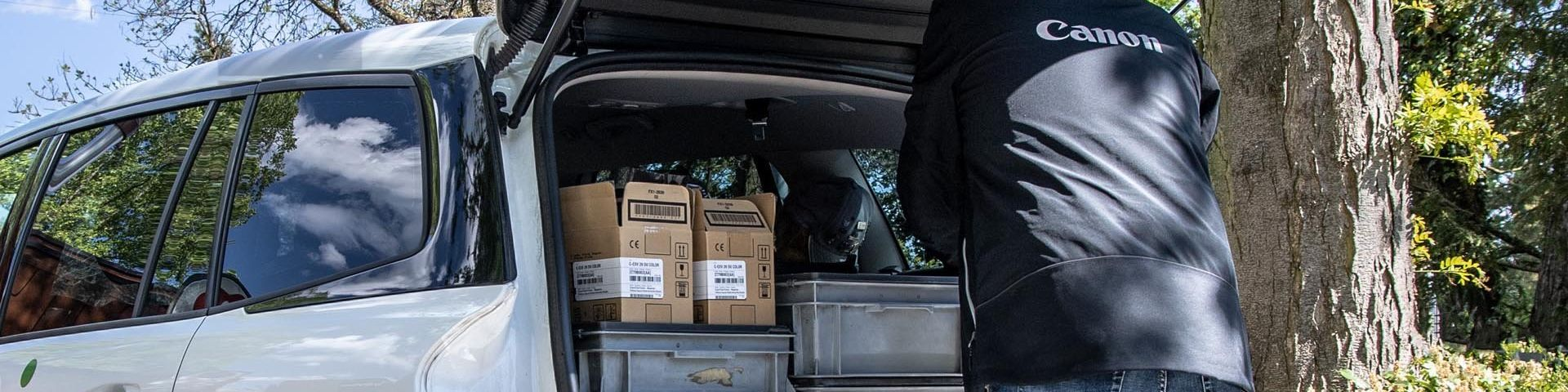 A Canon Service Engineer in a branded jacket unloads their equipment from the back of a white estate vehicle.